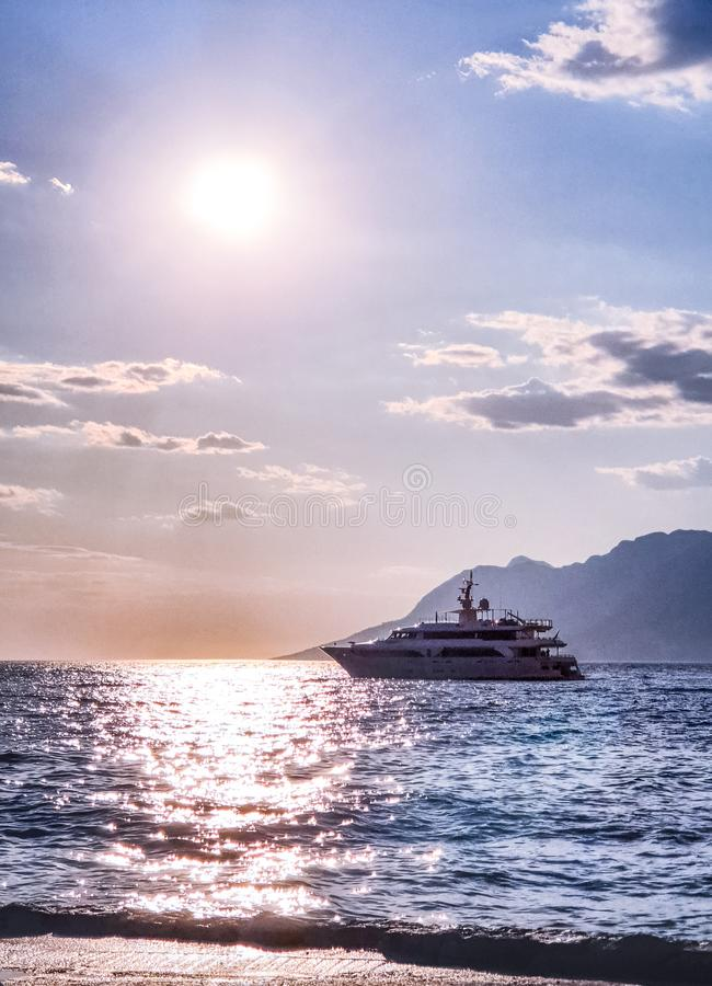 Paesaggio del mare adriatico: un yacht in un mare calmo su un fondo del tramonto e delle montagne fotografia stock