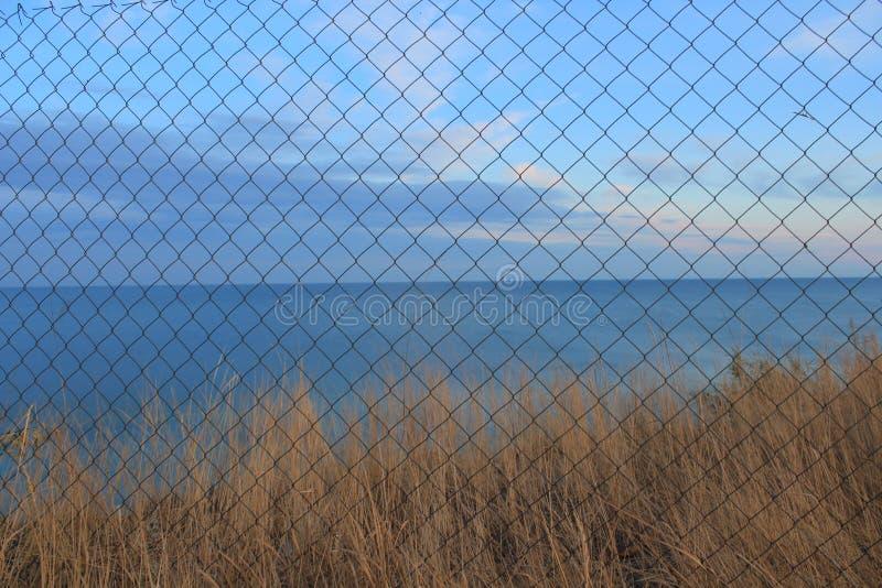 Paesaggio del mare dietro la griglia fotografie stock libere da diritti