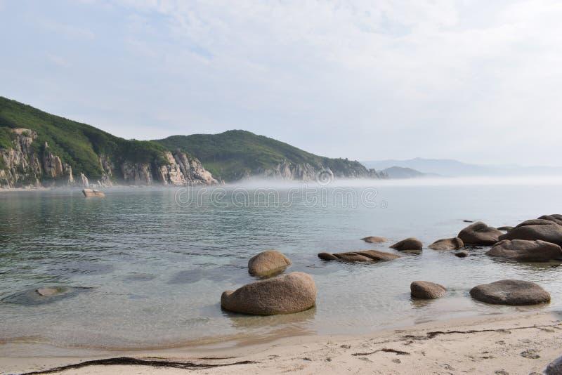 Paesaggio del mare, montagne, nebbia sopra l'acqua nel primo mattino fotografia stock libera da diritti