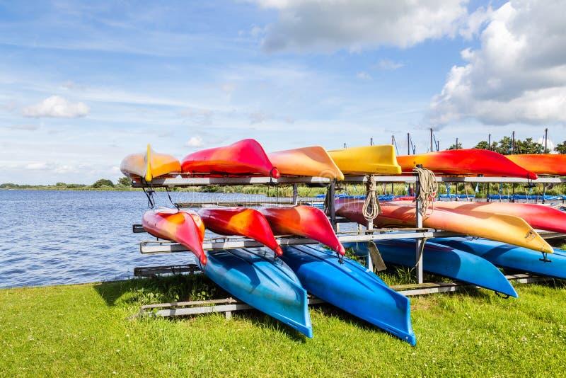 Paesaggio dell'acqua con le canoe locative variopinte fotografie stock