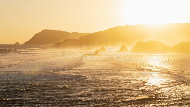 Paesaggio dell'oceano di tramonto con le onde, colline stratificate fotografia stock