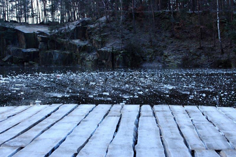 Paesaggio della cava Bordi di legno nel gelo sul lago congelato in cava di pietra nell'inverno Lago congelato con ghiaccio ed il  fotografia stock