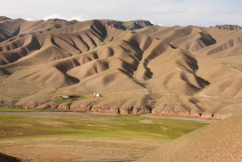 Paesaggio della montagna con i modelli naturali originali e una piccola azienda agricola distrutta fotografia stock