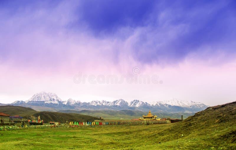 Paesaggio della montagna con il monastero tibetano dal pascolo di Tagong in Cina immagini stock