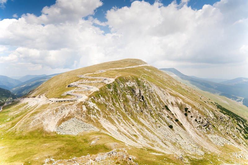 Paesaggio della montagna con la strada nel fondo fotografia stock libera da diritti