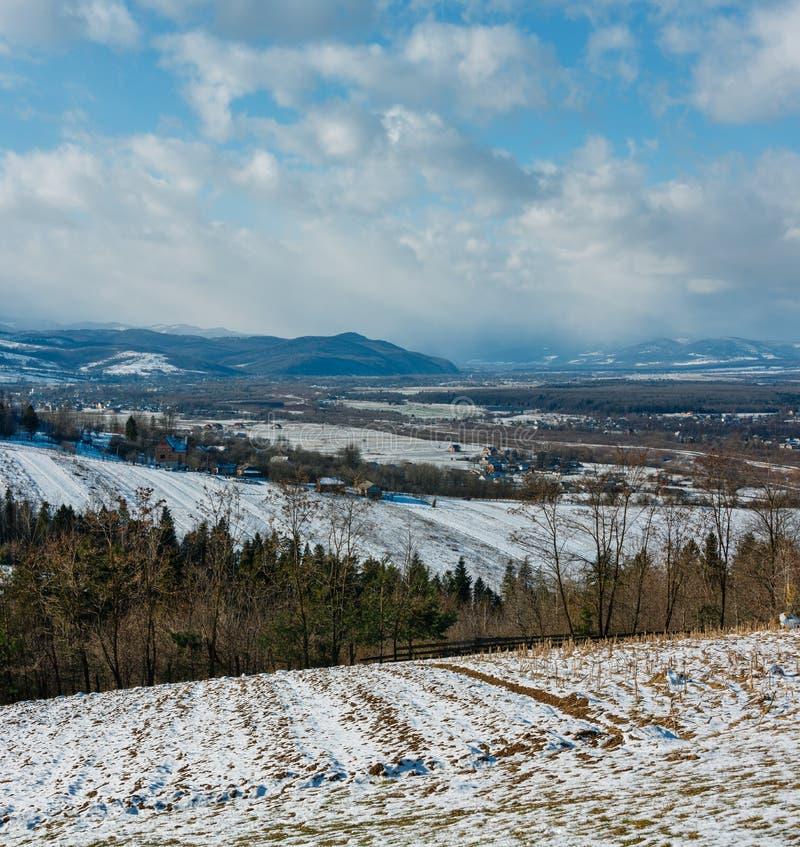 Paesaggio della montagna di inverno con il campo ed il villaggio immagini stock libere da diritti