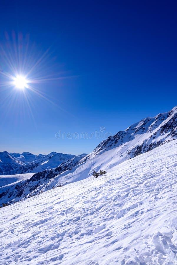 Paesaggio della montagna di inverno contro il cielo blu. fotografie stock