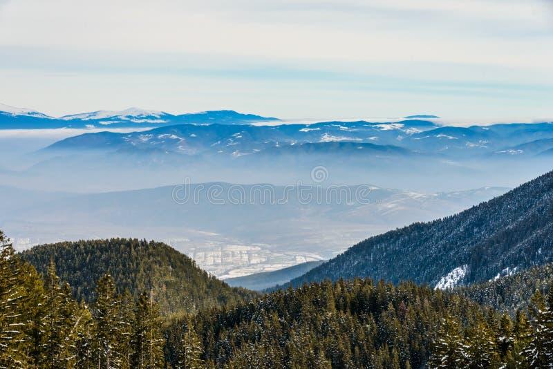 Paesaggio della montagna nel giorno gelido di inverno soleggiato con la chiara SK blu immagini stock