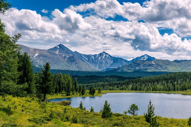 Paesaggio della montagna, nuvole bianche, lago e catena montuosa nella distanza Giorno soleggiato fantastico in montagne, grande  fotografie stock