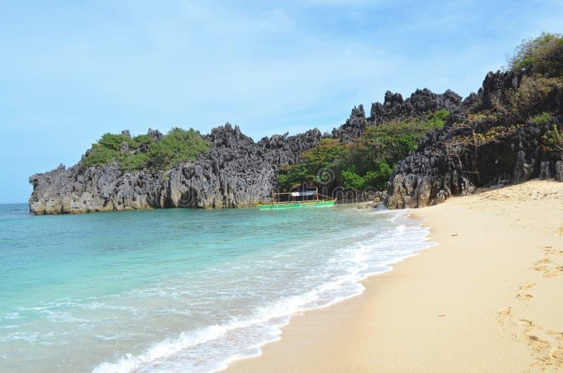 Paesaggio della natura: Spiaggia tropicale sabbiosa con una barca e un mare cristallino fotografia stock libera da diritti