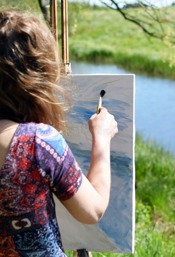 Paesaggio della pittura dell'artista della donna immagine stock libera da diritti