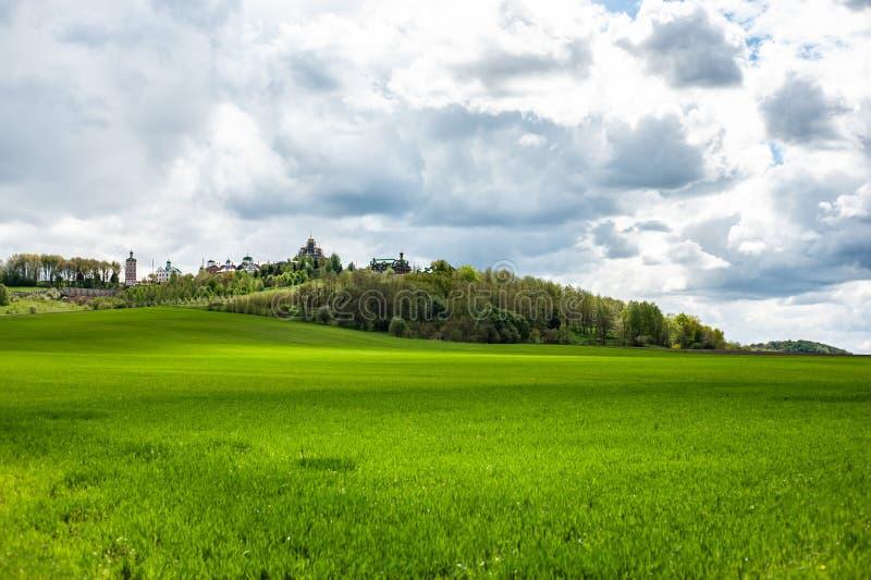 Paesaggio della primavera con erba verde, le colline e gli alberi, cielo nuvoloso fotografie stock