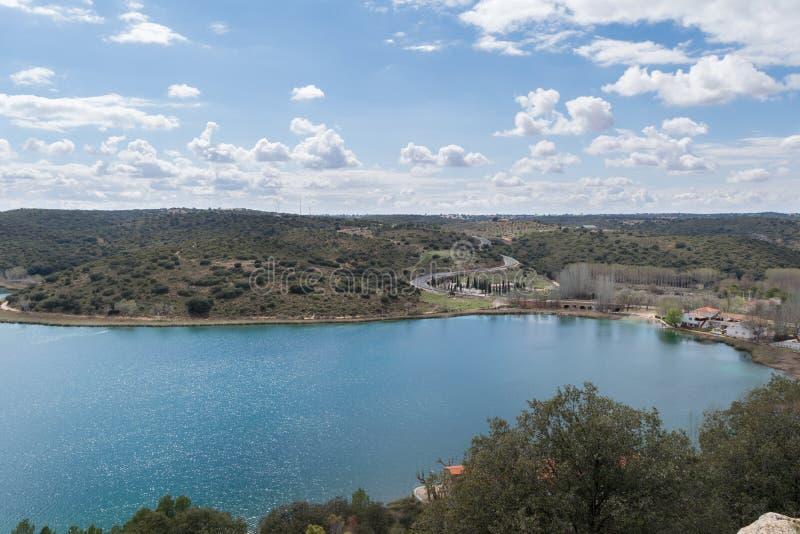 Paesaggio della primavera in cui i colori del blu e di verde predominano, con un lago come l'elemento principale fotografie stock