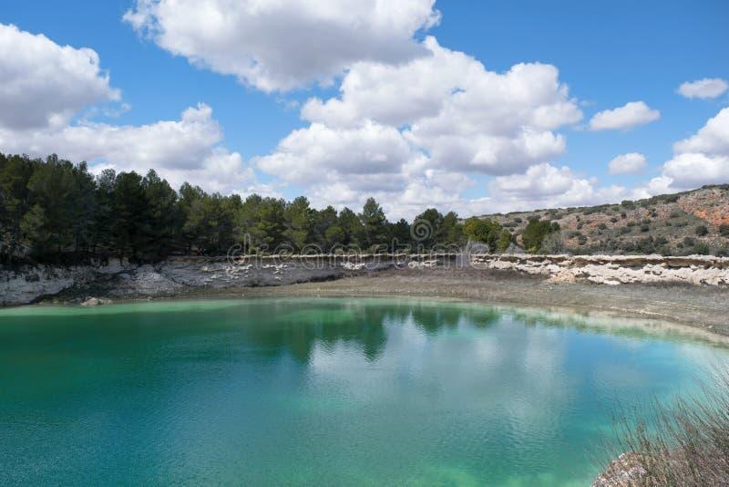 Paesaggio della primavera in cui i colori del blu e di verde predominano, con un lago come l'elemento principale fotografia stock