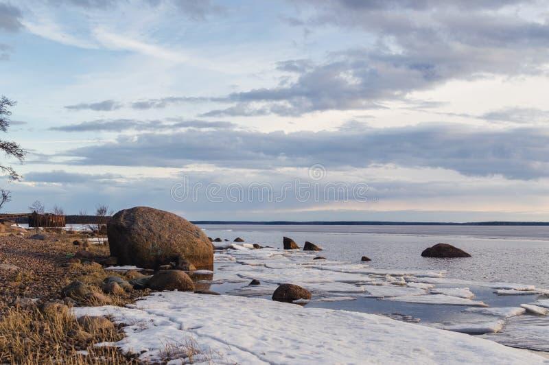 Paesaggio della riva del lago di inverno di sera con ora e ghiaccio, cielo nuvoloso blu Lago ladoga immagini stock libere da diritti
