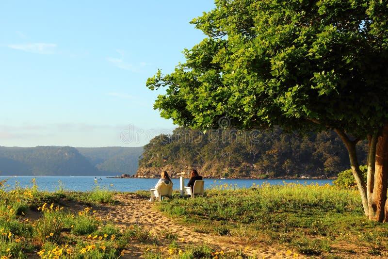 Paesaggio della riva in primavera con le donne a riposo fotografia stock libera da diritti
