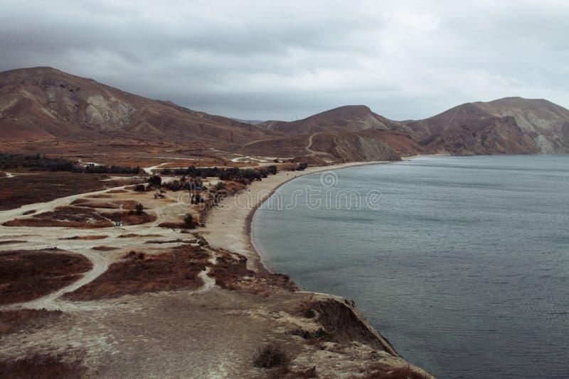 Paesaggio della riva della spiaggia, montagne Kara-Dag nel giorno di inverno del sud Mar Nero, Koktebel, Crimea fotografia stock