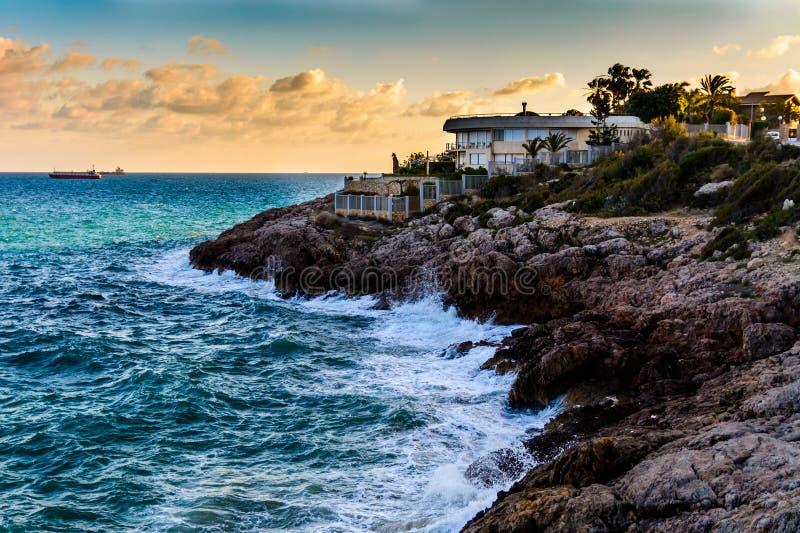 Paesaggio della spiaggia rocciosa al tramonto in Spagna fotografia stock