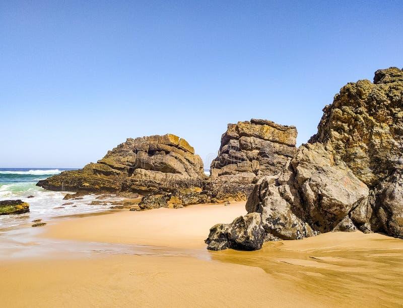 Paesaggio della spiaggia sabbiosa di Adraga con le pietre vicino a Sintra fotografie stock libere da diritti