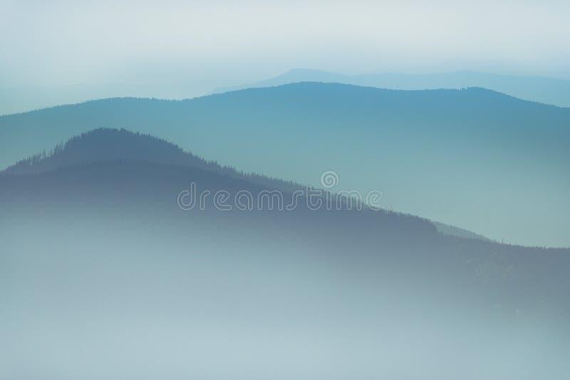 Paesaggio delle colline della montagna nebbiosa Vista degli strati delle montagne e della foschia nelle valli immagine stock