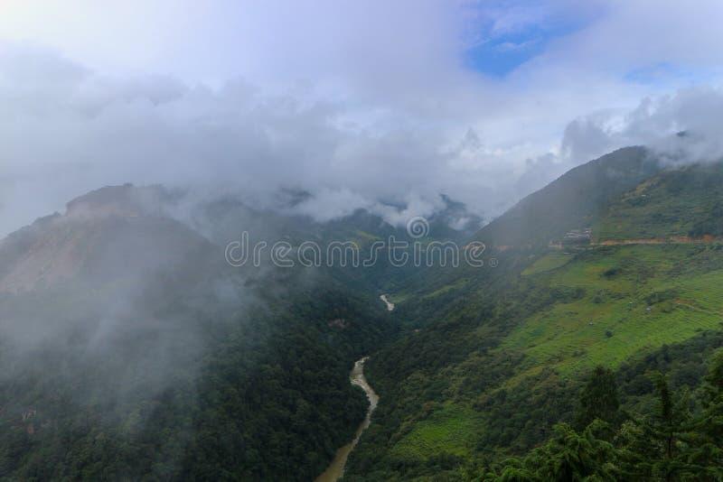 Paesaggio delle colline e del fiume nebbiosi di Mangde in Bumthang, Bhutan immagine stock libera da diritti