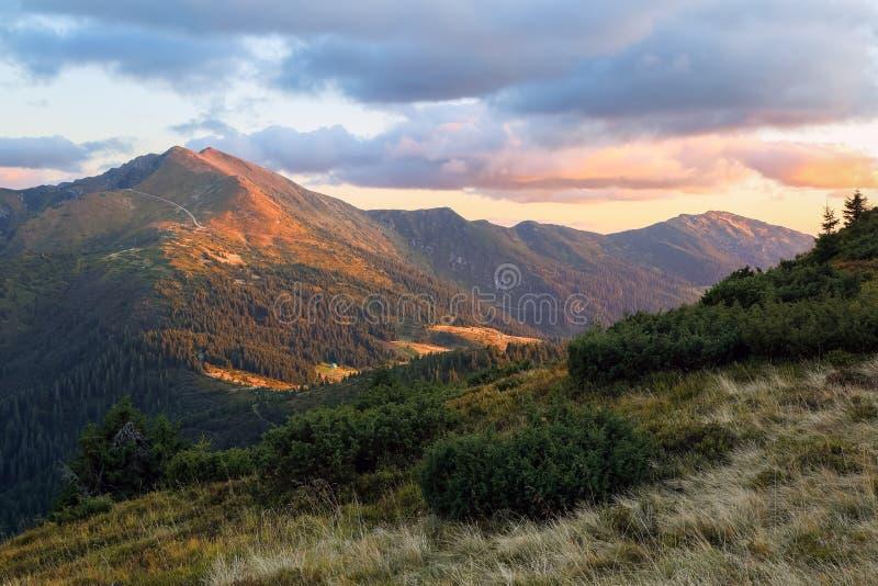 Paesaggio delle montagne con un bel tramonto, cielo nuvoloso e orizzonte colorato d'arancia Felice autunno Luogo turistico di Car fotografia stock