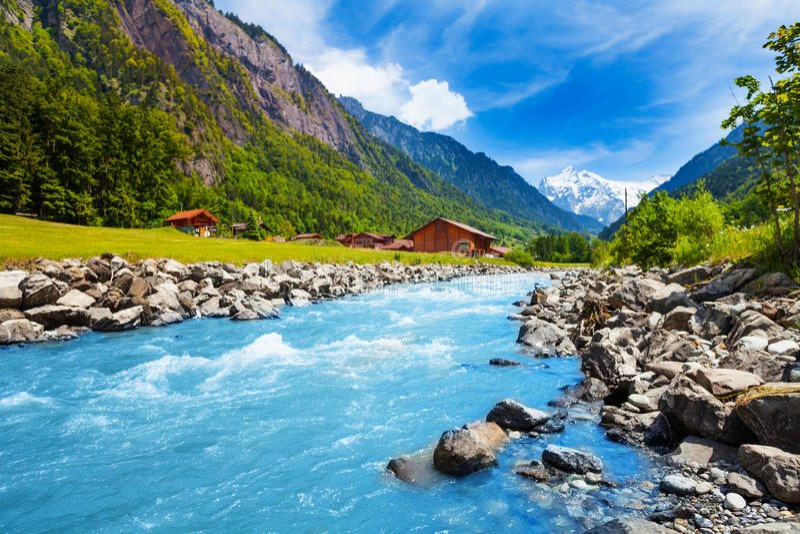 Paesaggio dello svizzero con la corrente e le case del fiume fotografia stock libera da diritti
