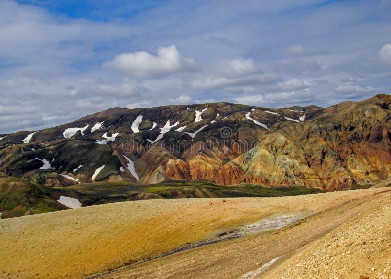 Paesaggio di area geotermica di Landamannalaugar con le montagne colorate della riolite, giacimenti di lava neri, neve e vegetazi fotografia stock