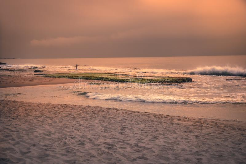 Paesaggio di paesaggio delle onde della spuma dell'oceano della spiaggia di tramonto con il cielo ed il pescatore arancio drammat immagine stock