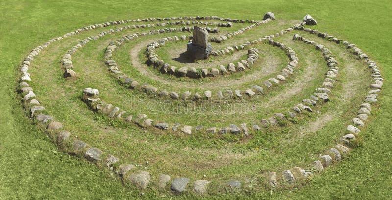 Paesaggio di estate con un labirinto di pietra su un prato inglese verde fotografie stock libere da diritti