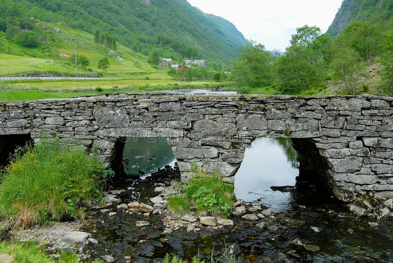 Paesaggio di estate con un vecchio ponte di pietra attraverso il piccolo fiume in Norvegia rurale fotografia stock libera da diritti