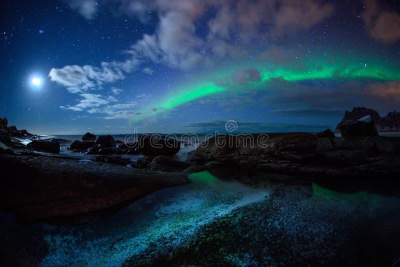 Paesaggio di inverno con Aurora Borealis e la luna piena luce nordica s nell'arcipelago di Lofoten, Norvegia fotografie stock