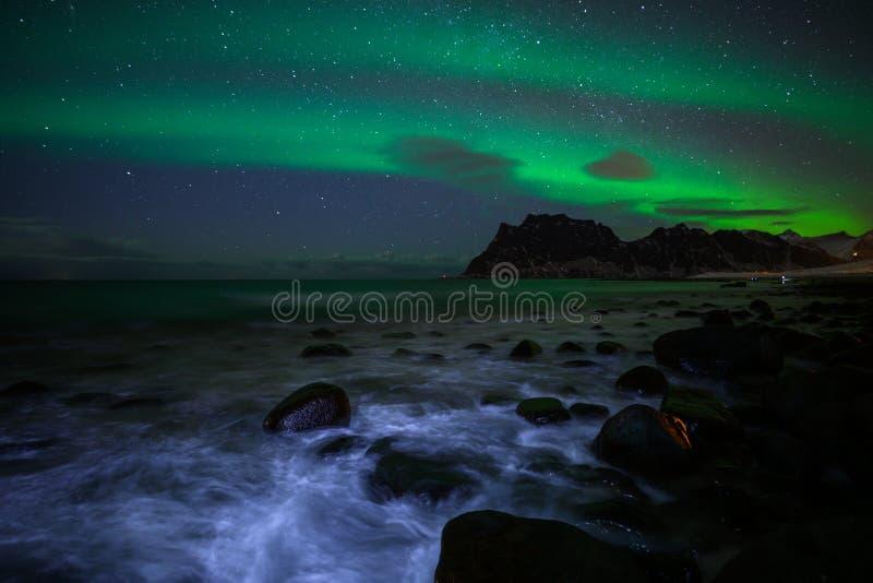 Paesaggio di inverno con Aurora Borealis e la luna piena luce nordica s nell'arcipelago di Lofoten, Norvegia immagini stock