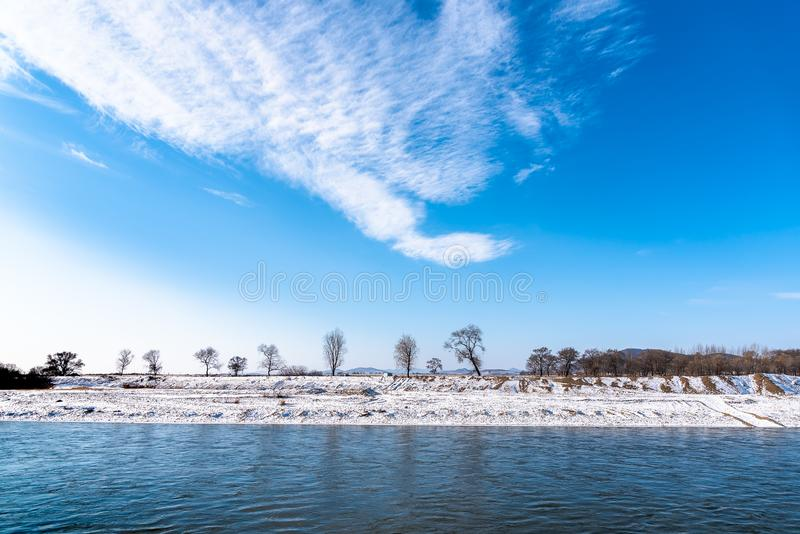 Paesaggio di inverno con gli alberi, fiume e foresta, albero asciutto senza foglia con cielo blu, nuvola e la neve coperta a terr immagine stock