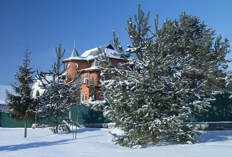 Paesaggio di inverno con il cottage sul fondo del blu di giro fotografia stock libera da diritti