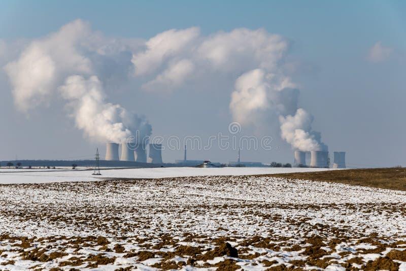 Paesaggio di inverno con la centrale atomica sull'orizzonte fotografia stock