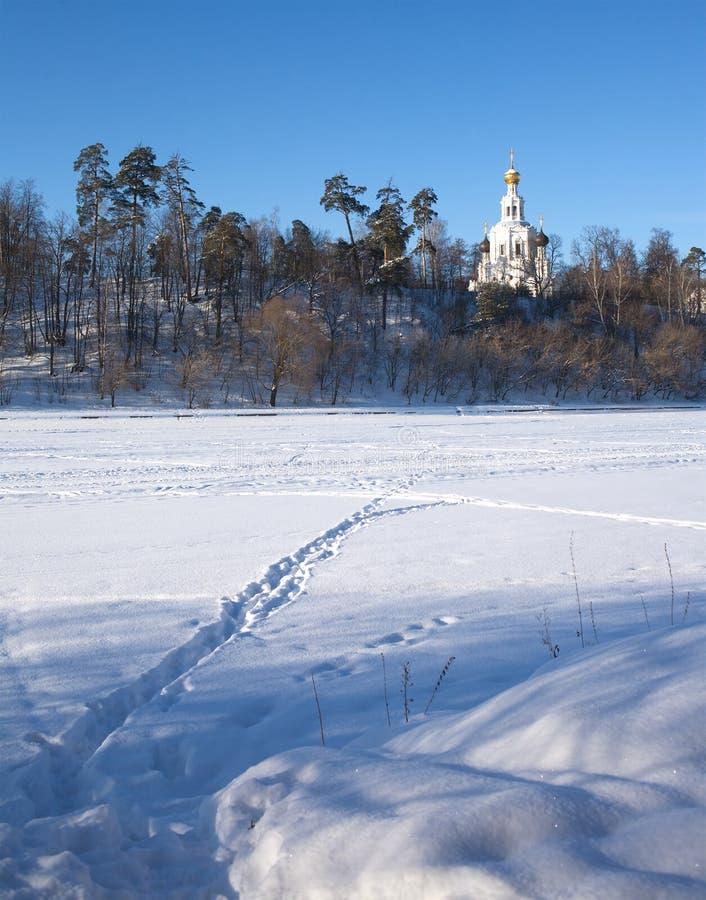 Paesaggio di inverno con la chiesa russa sulla collina immagini stock libere da diritti