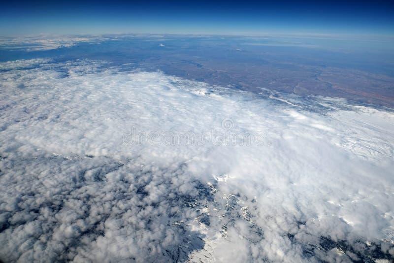 Paesaggio di inverno con la vista della neve, della terra e delle nuvole dall'aeroplano volante fotografia stock libera da diritti