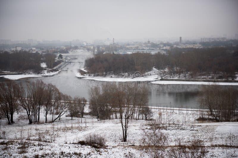 Paesaggio di inverno dei campi, degli alberi e del fiume innevati nella mattina nebbiosa in anticipo immagine stock