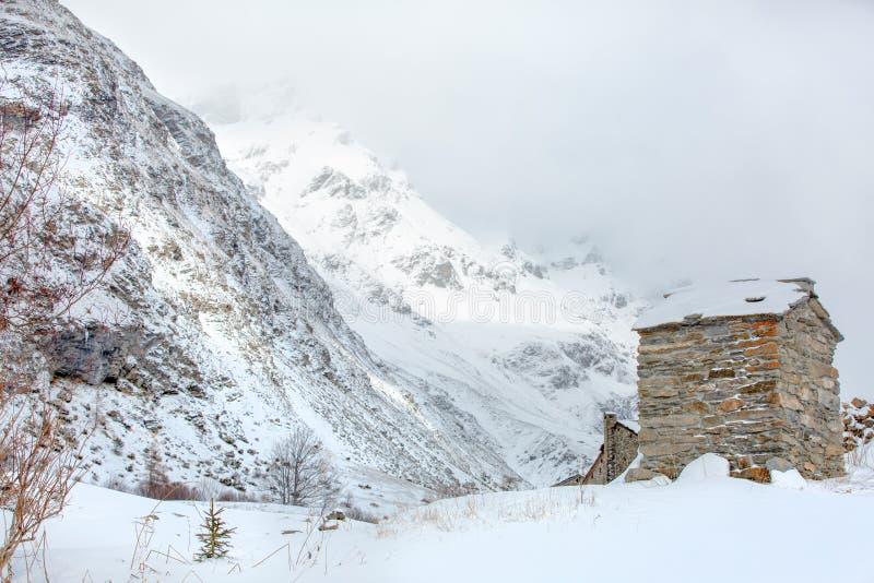 Paesaggio di inverno della montagna sull'orlo di un Highland Village con le nuvole basse e le riflessioni del sole fotografia stock