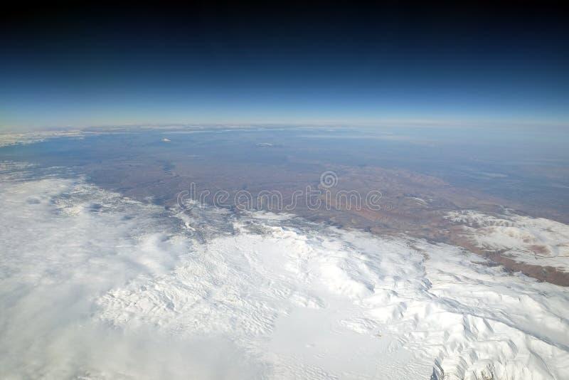 Paesaggio di inverno delle montagne della neve dall'aereo in stratosfera con il cielo blu scuro fotografia stock
