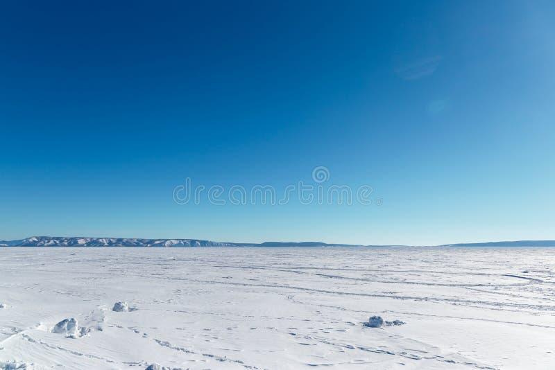 Paesaggio di inverno Lago congelato un chiaro giorno di inverno Lago congelato con le montagne fotografia stock libera da diritti