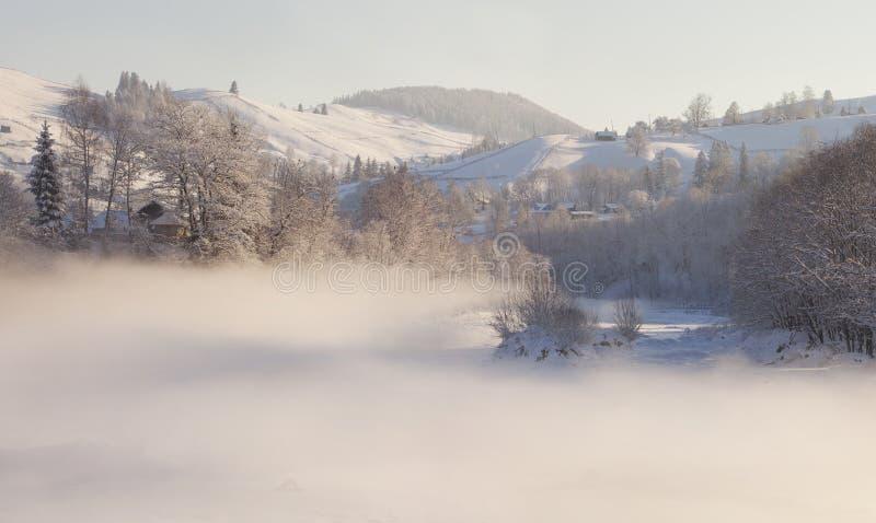 Paesaggio di inverno nel paesino di montagna. Mornin nebbioso immagine stock libera da diritti