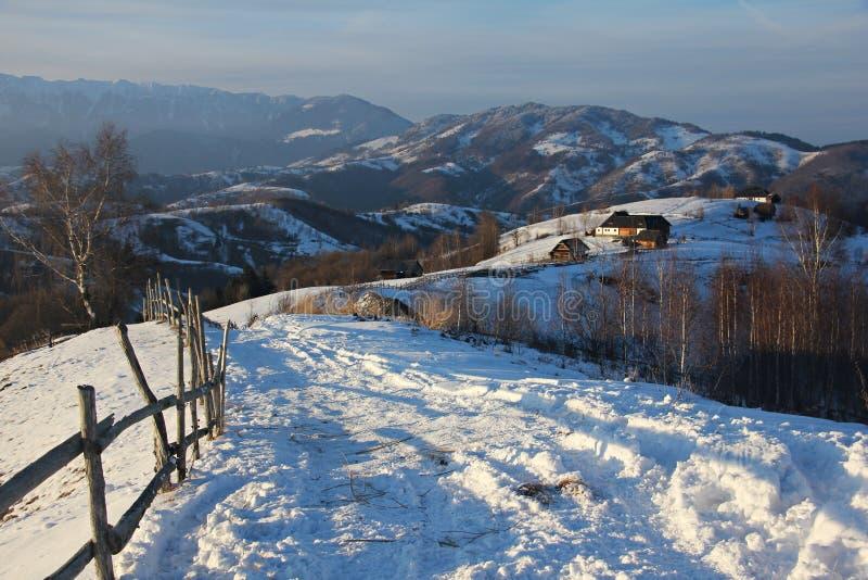 Paesaggio di inverno nelle montagne - con la piccola strada campestre tradizionale e del villaggio fotografia stock