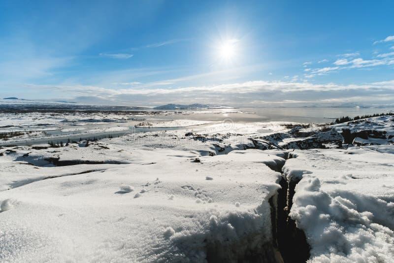 Paesaggio di inverno, terra innevata incrinata con il sole su cielo blu, al parco nazionale di Pingvellir in Islanda fotografia stock