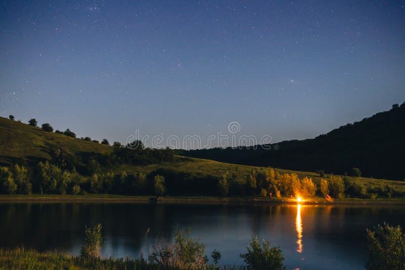Paesaggio di notte con il cielo di campeggio della stella e del falò, fiume e montagne, notte che pesca concetto, fuoco di accam fotografia stock