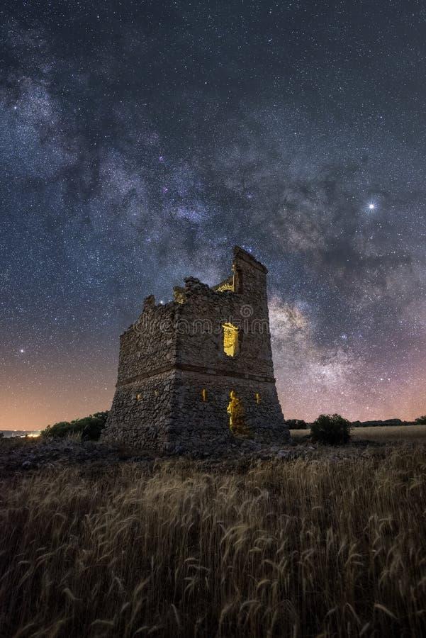 Paesaggio di notte con la Via Lattea sopra un vecchio castello immagine stock