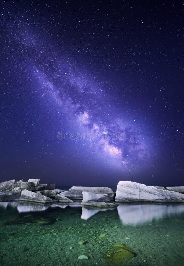 Paesaggio di notte con la Via Lattea variopinta al mare con le pietre Cielo stellato Fondo dello spazio immagini stock libere da diritti