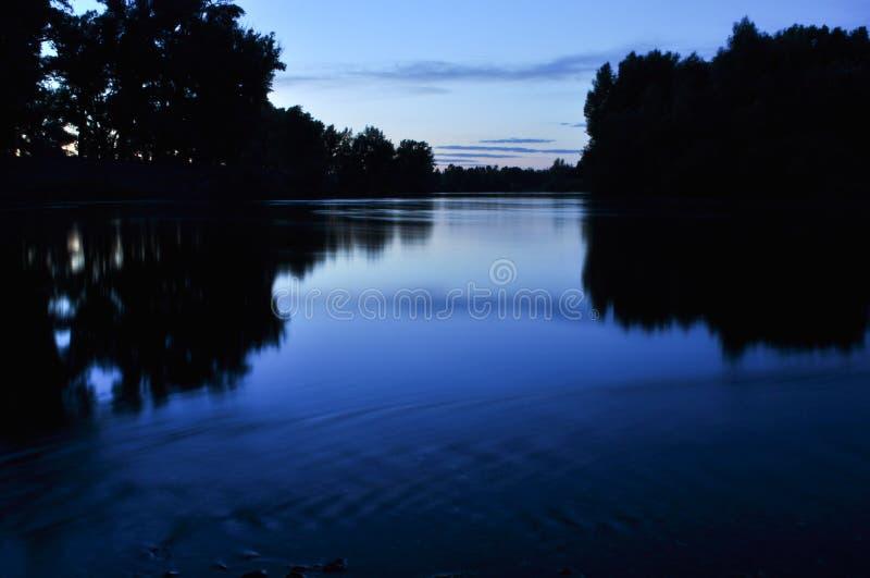 Paesaggio di notte Fiume calmo al crepuscolo immagine stock