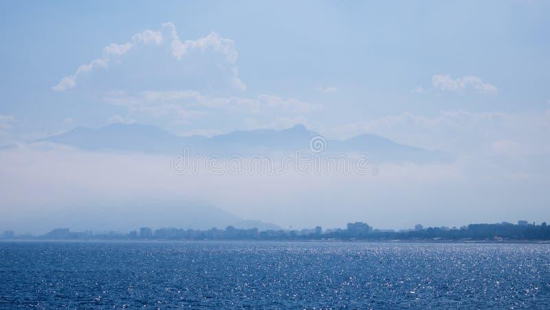 Paesaggio di stupore, con la città di Adalia in Turchia, mar Mediterraneo che scintillano al sole, nuvole bianche, cielo blu e fotografia stock libera da diritti